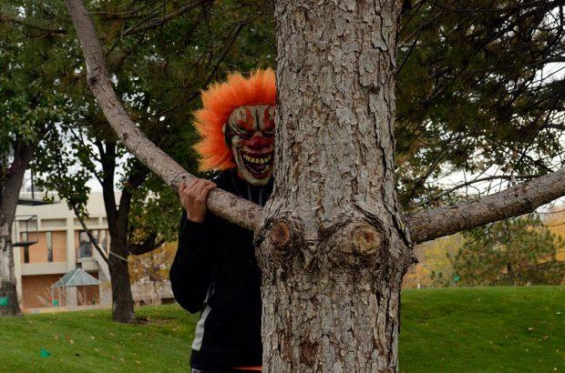 Creepy clown behind a tree