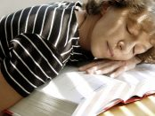 Tired girl sleeping on her book