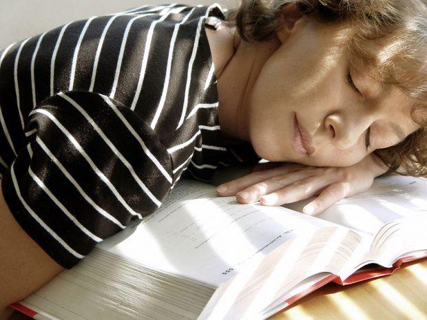 Tired girl sleeping on her book
