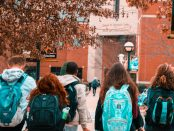 Students wearing backpacks walk to class