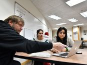 A male tutor assists two female students