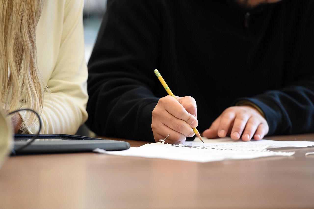 Student writing beside a tutor