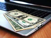 Dollar bills on a laptop