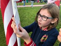 Young girl reads a note attached to American flag