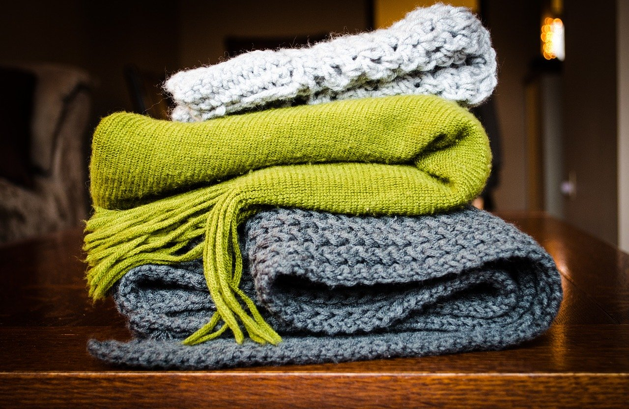 Knitted hat, scarf and blanket piled together