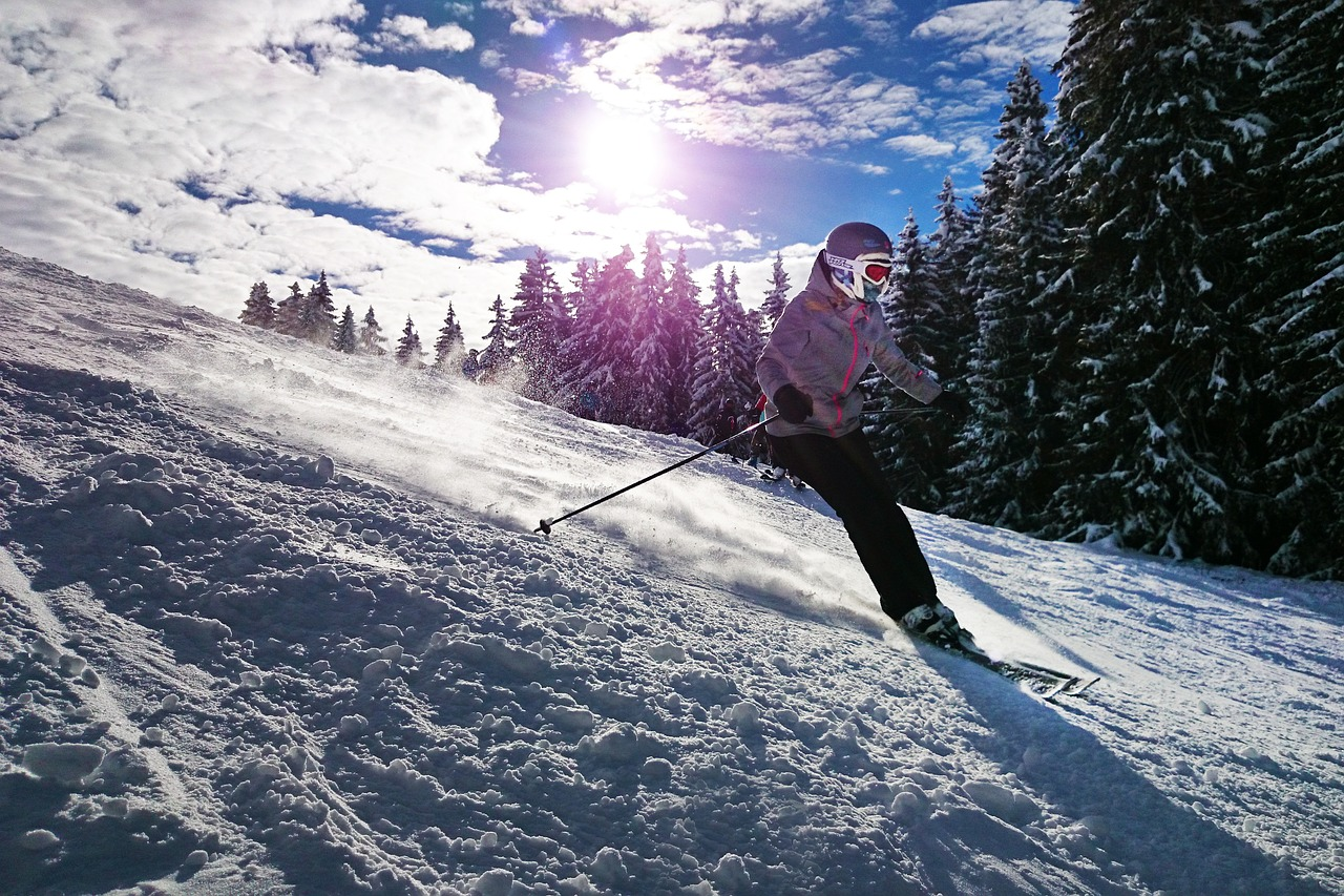 Girl skiing downhill on a sunny day