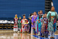 Native American dancers stand in a row