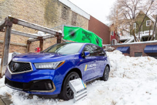 Blue Acura MDX surrounded by snow