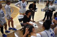 Players gather around Coach Grayer