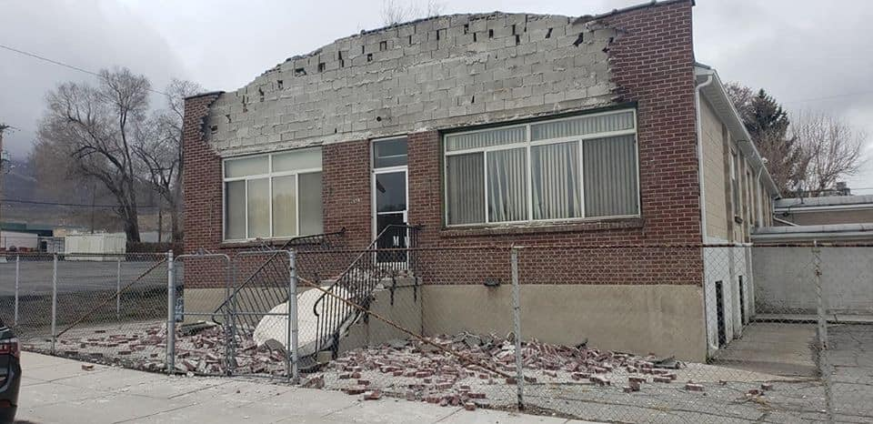Facade scattered on ground in front of old building