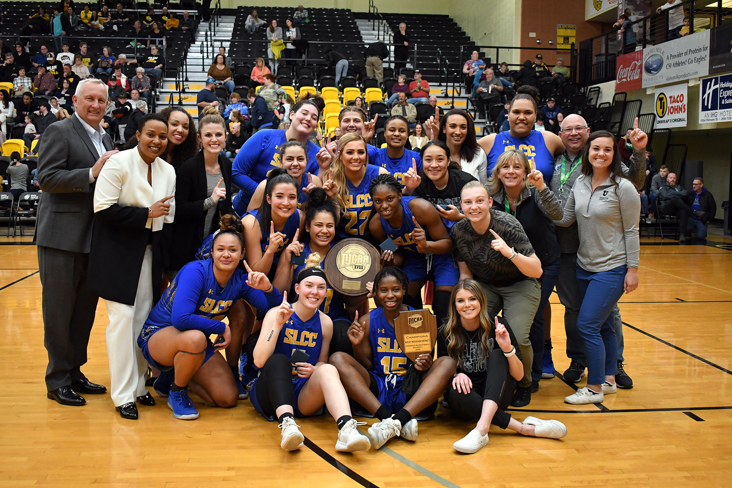 Women's basketball team with championship plaque