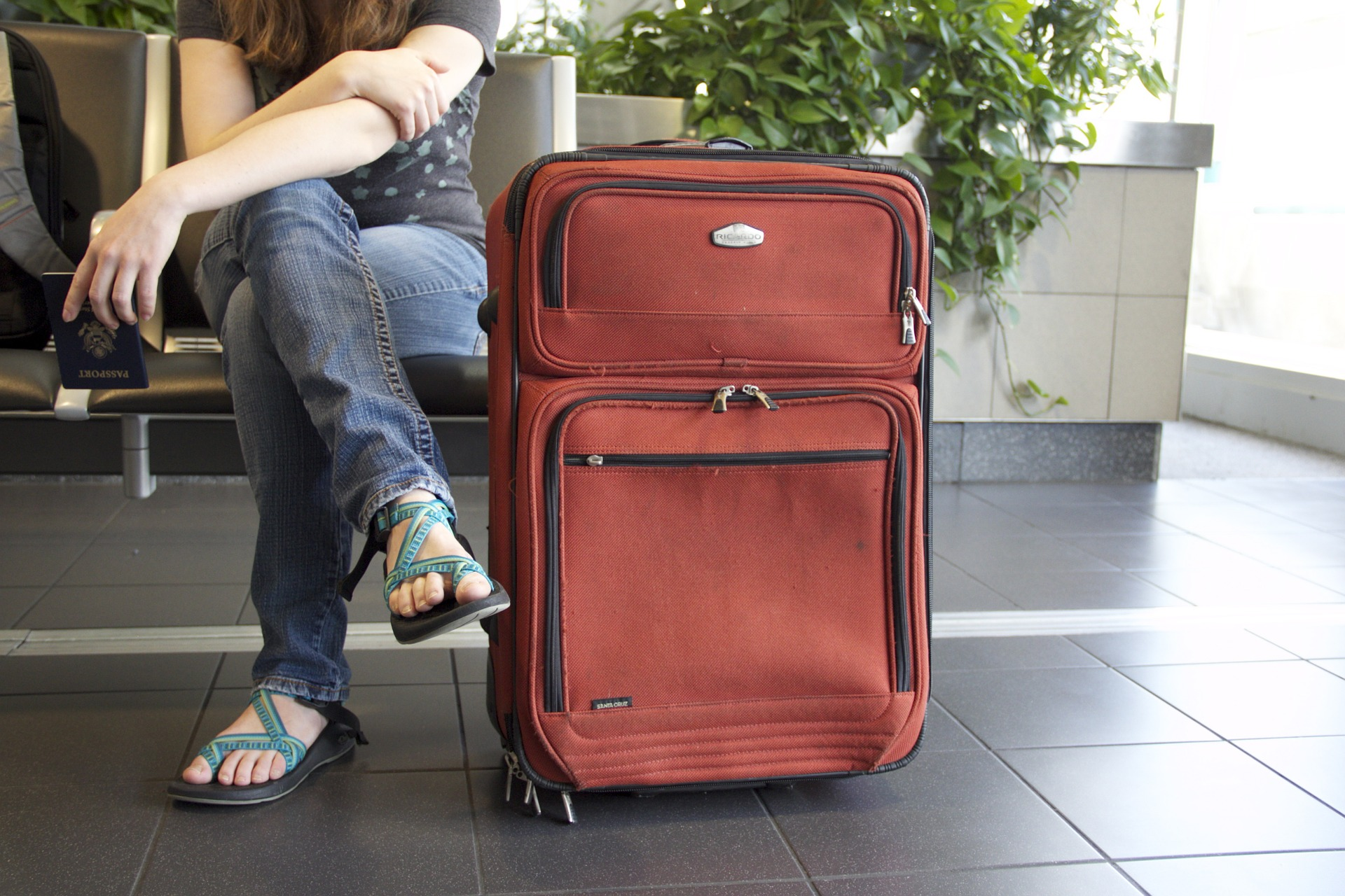 Traveler sits next to luggage while holding passport