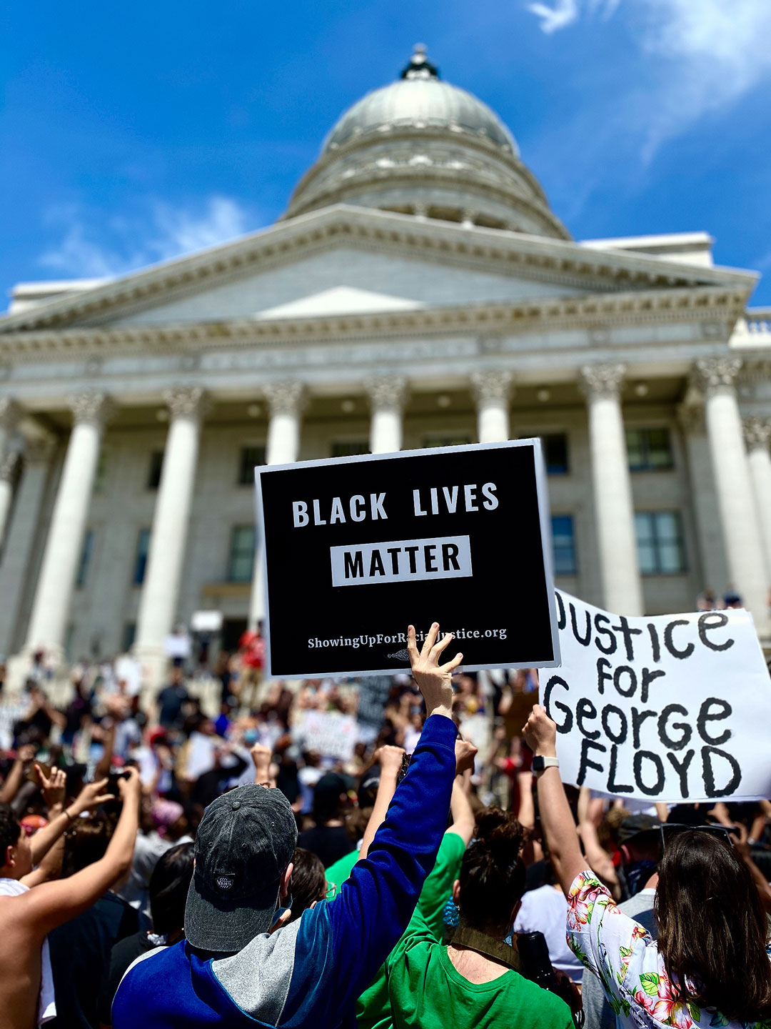 """Protesters hold """"Justice for George Floyd"""" and """"Black Lives Matter"""" signs"""