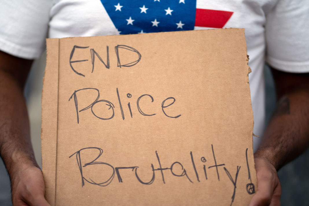 """Sign reads """"End police brutality!"""""""