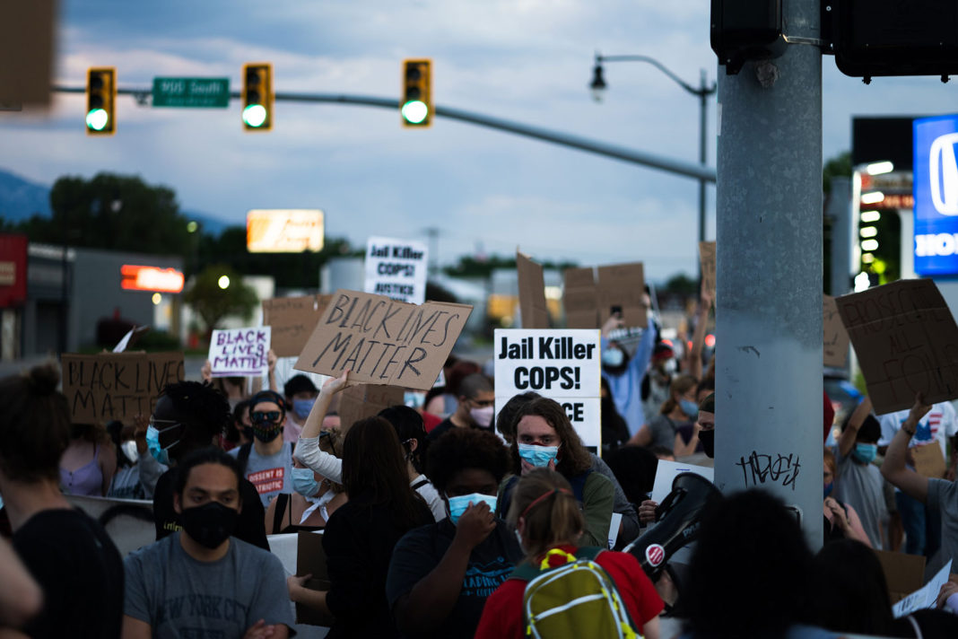 Protesters carry signs in downtown Salt Lake City