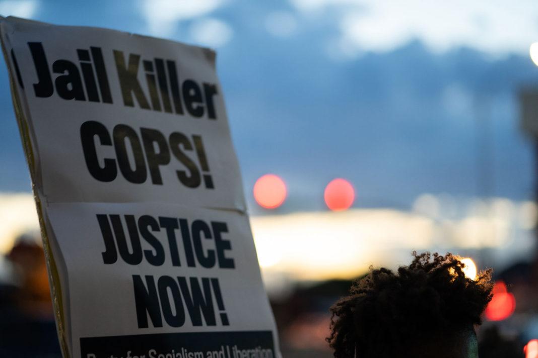 "Sign reads ""Jail Killer COPS! JUSTICE NOW!"""