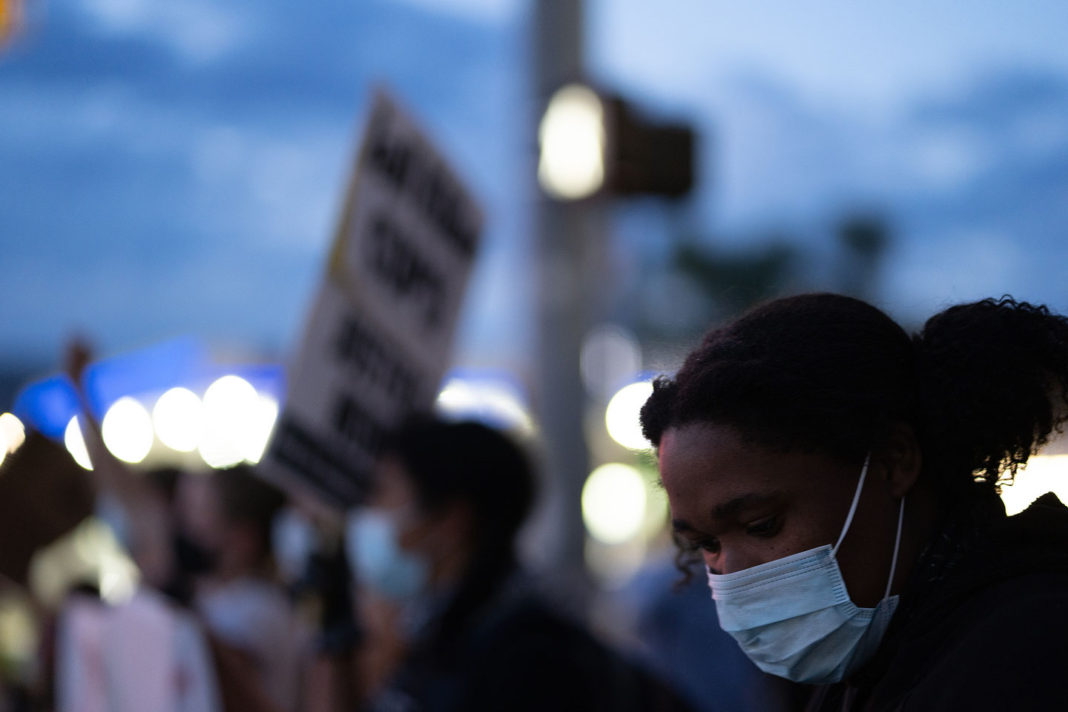 Young protester wearing mask