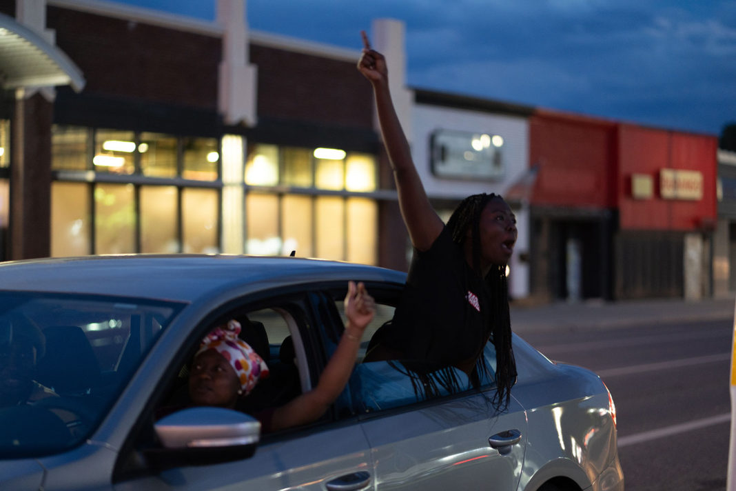 Young woman shouting out of car window