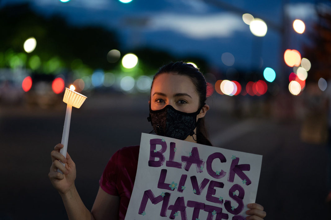"""Woman holds lit candle and """"Black Lives Matter"""" sign"""