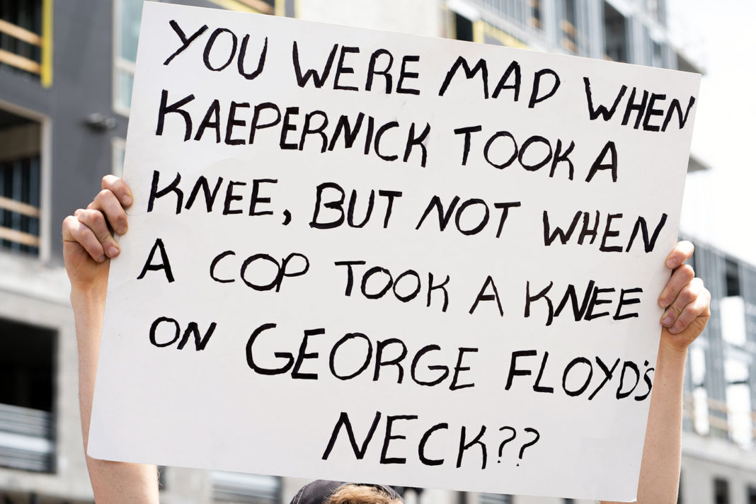 """Sign reads """"You were mad when Kaepernick took a knee, but not when a cop took a knee on George Floyd's neck??"""""""