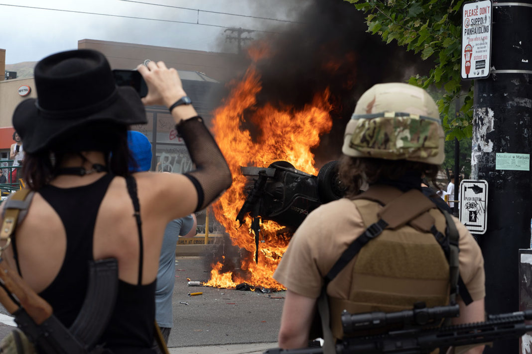 Protesters watch burning car