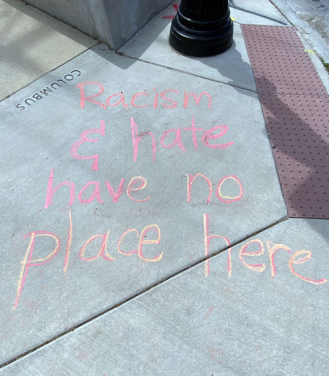 """Chalk reads """"Racism and hate have no place here"""""""