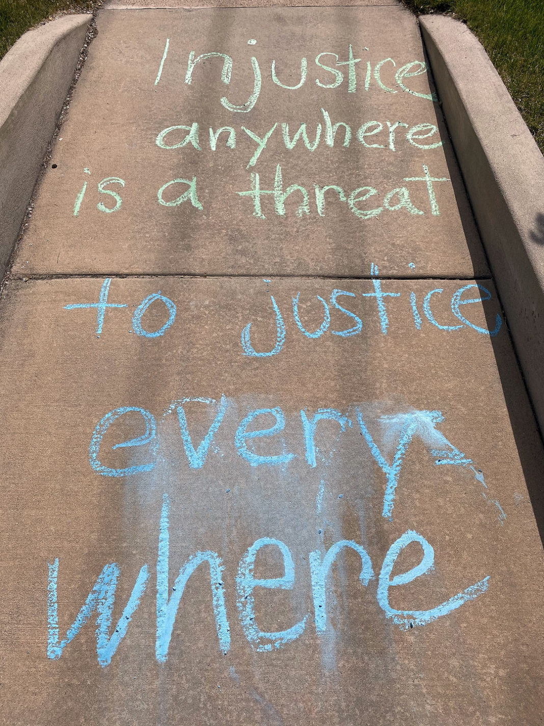 """Chalk reads """"Injustice anywhere is a threat to justice everywhere"""""""