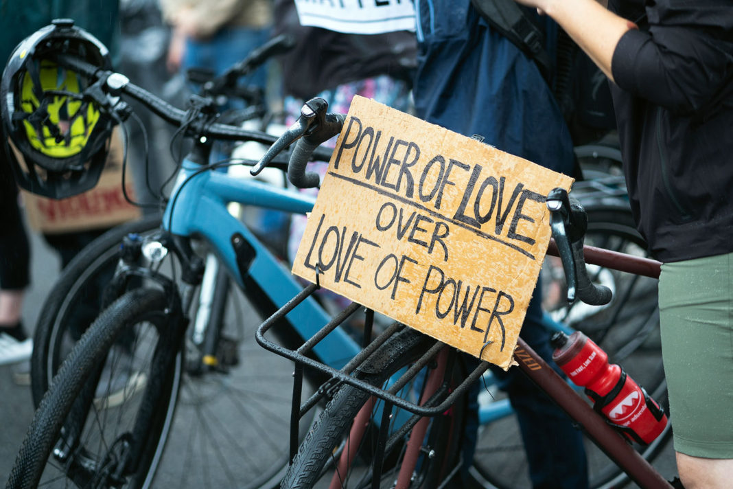 """Sign reads """"Power of love over love of power"""""""
