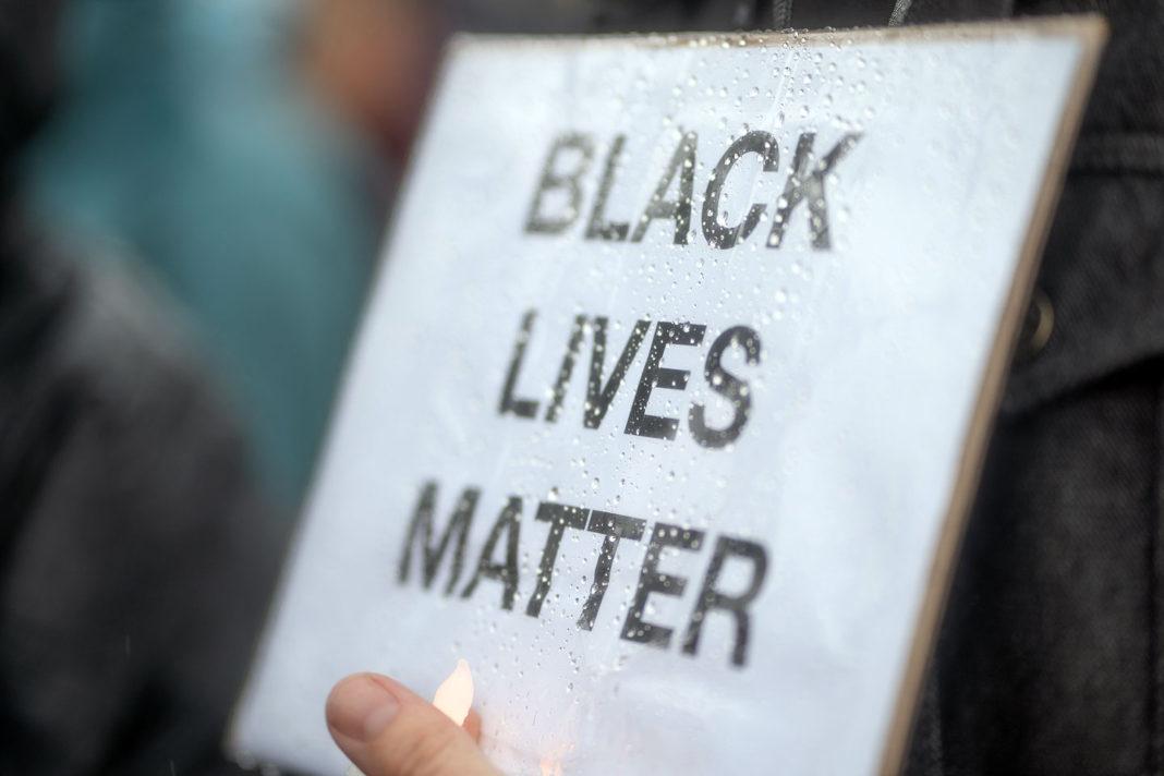 Black Lives Matter sign covered in rain droplets