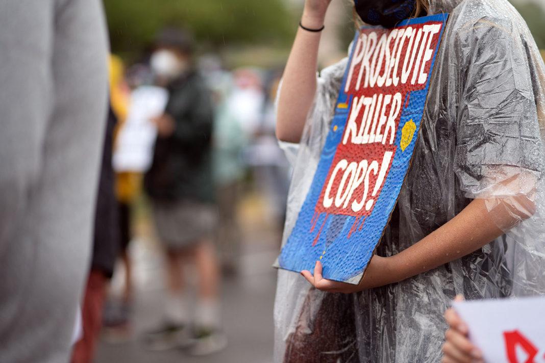 "Sign reads ""Prosecute killer cops!"""