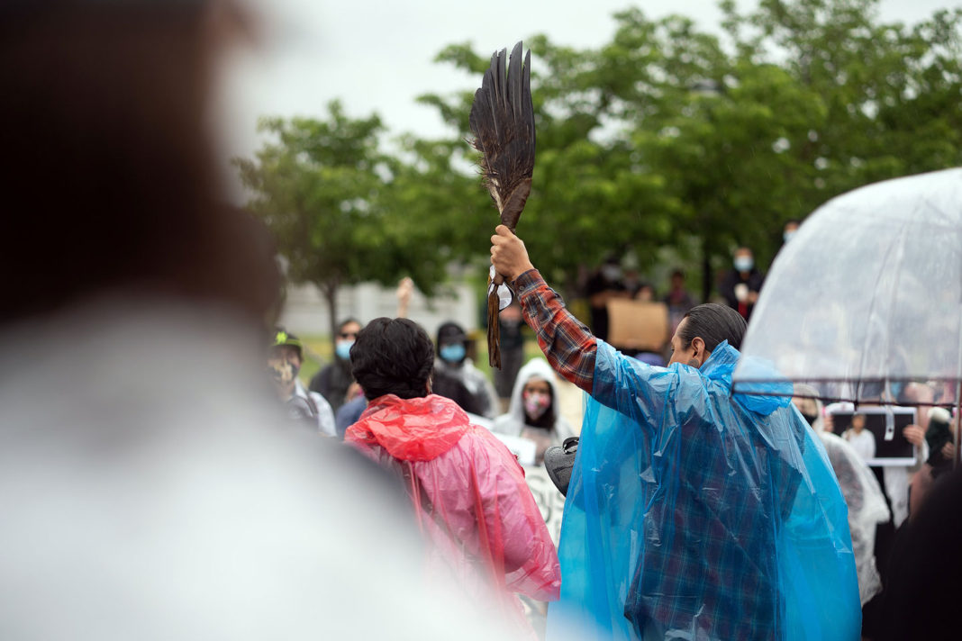 Man in blue poncho holds eagle feathers in the air