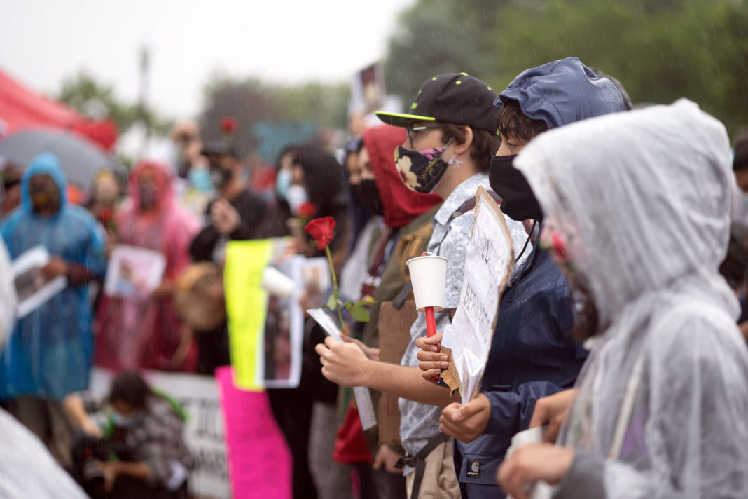 Rain-soaked protesters hold flowers, candles and signs