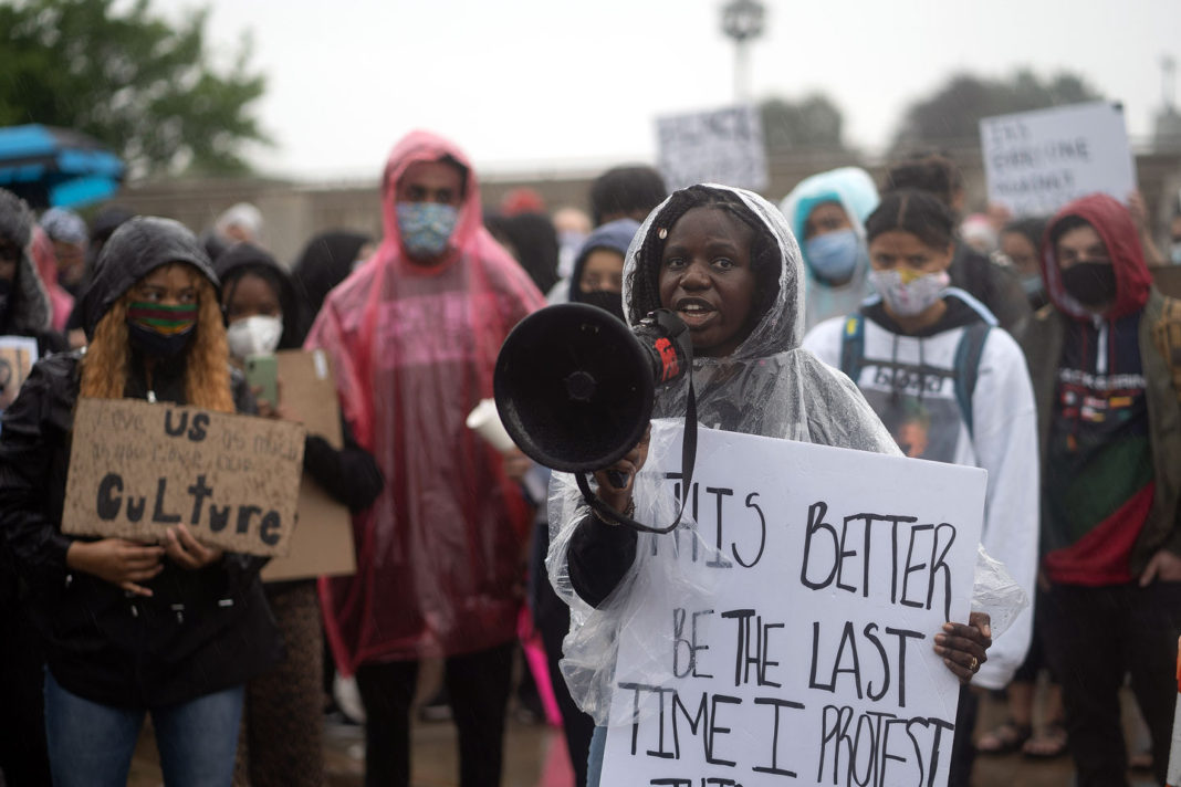 """Woman carries sign that reads """"This better be the last time I protest this"""""""