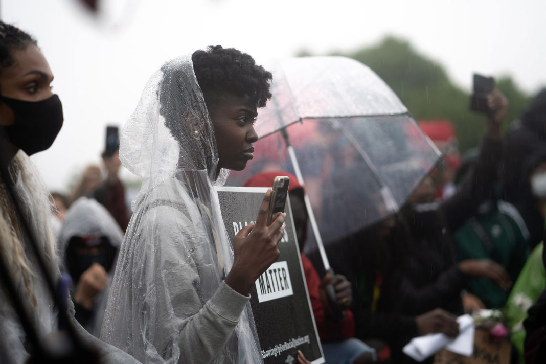 Protester wears a poncho while recording demonstration
