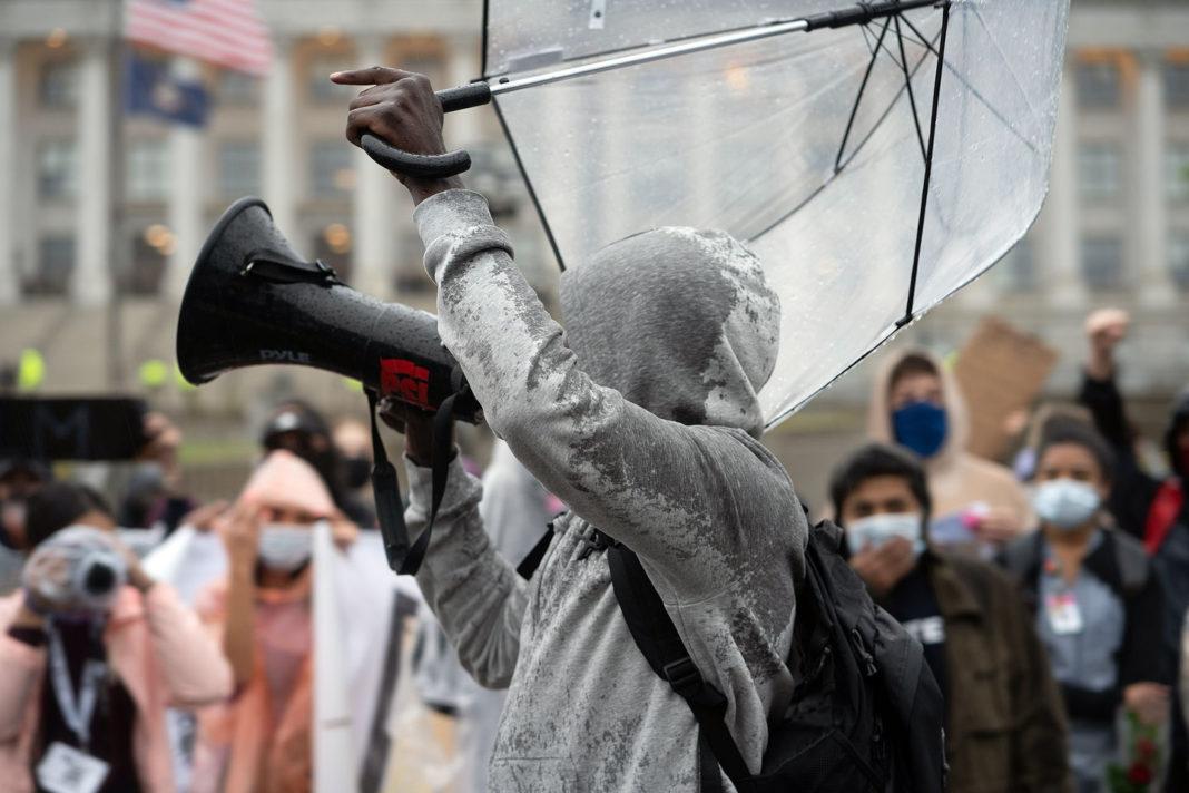Protester holding megaphone and umbrella