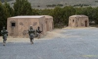 Cadets move behind an outbuilding