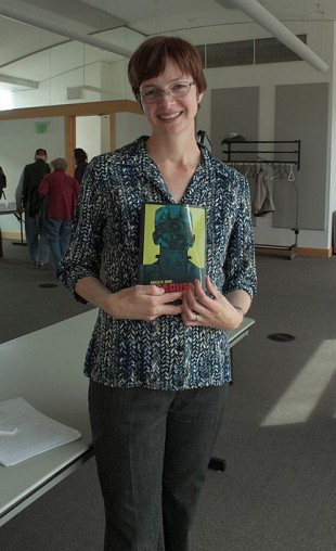 The speaker, Angela Smith, holding a copy of her book.