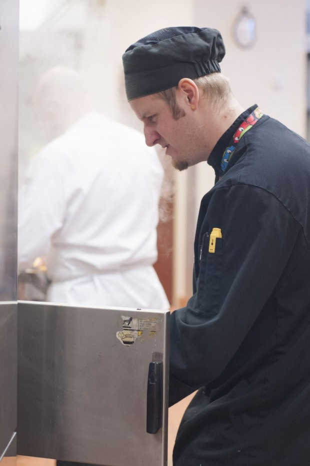 A culinary student is placing a pan into a oven during breakfast service at the Utah State Capitol cafeteria.