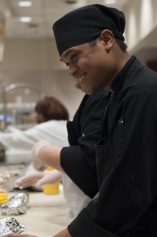 A culinary student at the Grill in the Utah State Capitol Cafeteria is smiling as they serve the breakfast rush crowd.