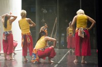 Dancers gathered in a circle backstage after rehearsal to discuss their performance.