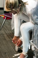 Dancer dressed in all white laces up white ballet shoes prior to her solo dance.