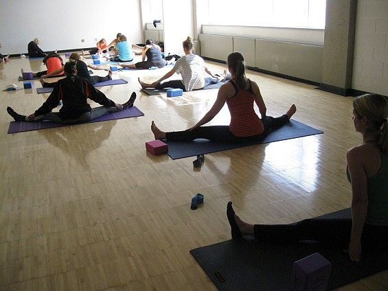 Paula Neilson-Williams (right) and her students practice yoga.