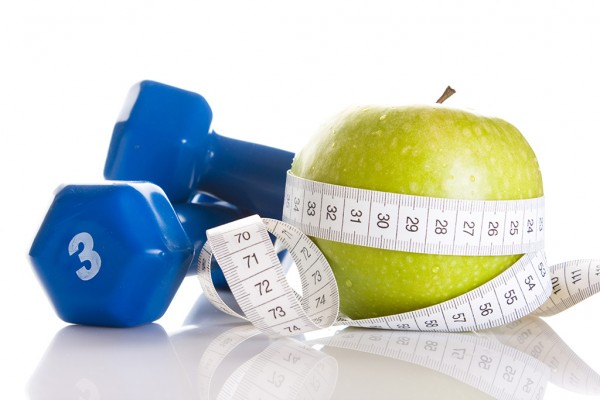 Apple, barbell and measuring tape