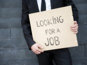 "Man holds a ""Looking for a job"" sign"