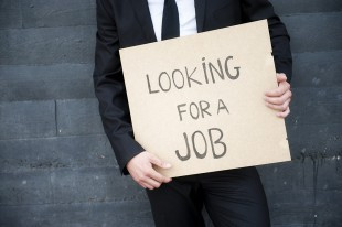 """Man holds a """"Looking for a job"""" sign"""