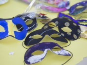 Completed masquerade masks sitting on a table in the shade of the trees