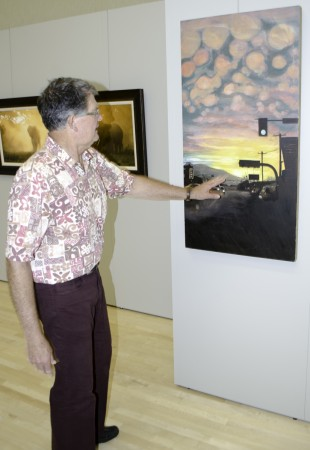 Gordon Storrs shows off one of the oil paintings entered into the art show.