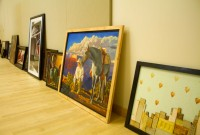 Paintings lined up wait their turn to be hung.