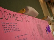Students write their thoughts about domestic violence during the Silent Witness display at Taylorsville Redwood Campus.