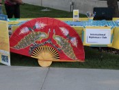 The International Diplomacy Club's table, decorated with presentation board, a map-themed table decoration, and a very large decorative fan.